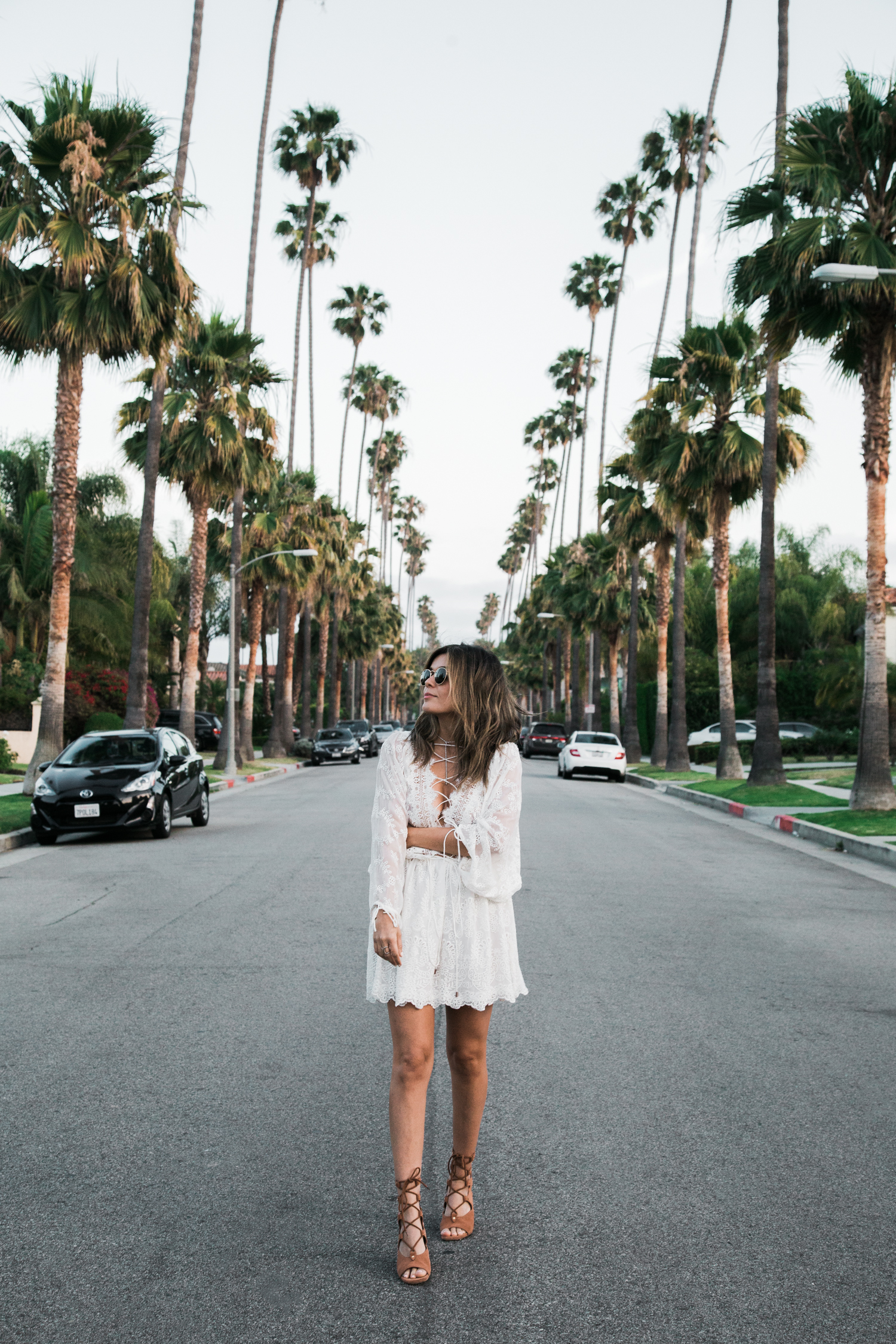 Sara Azani of Style MBA wears a white Zimmermann lace dress and Chloe Sandals