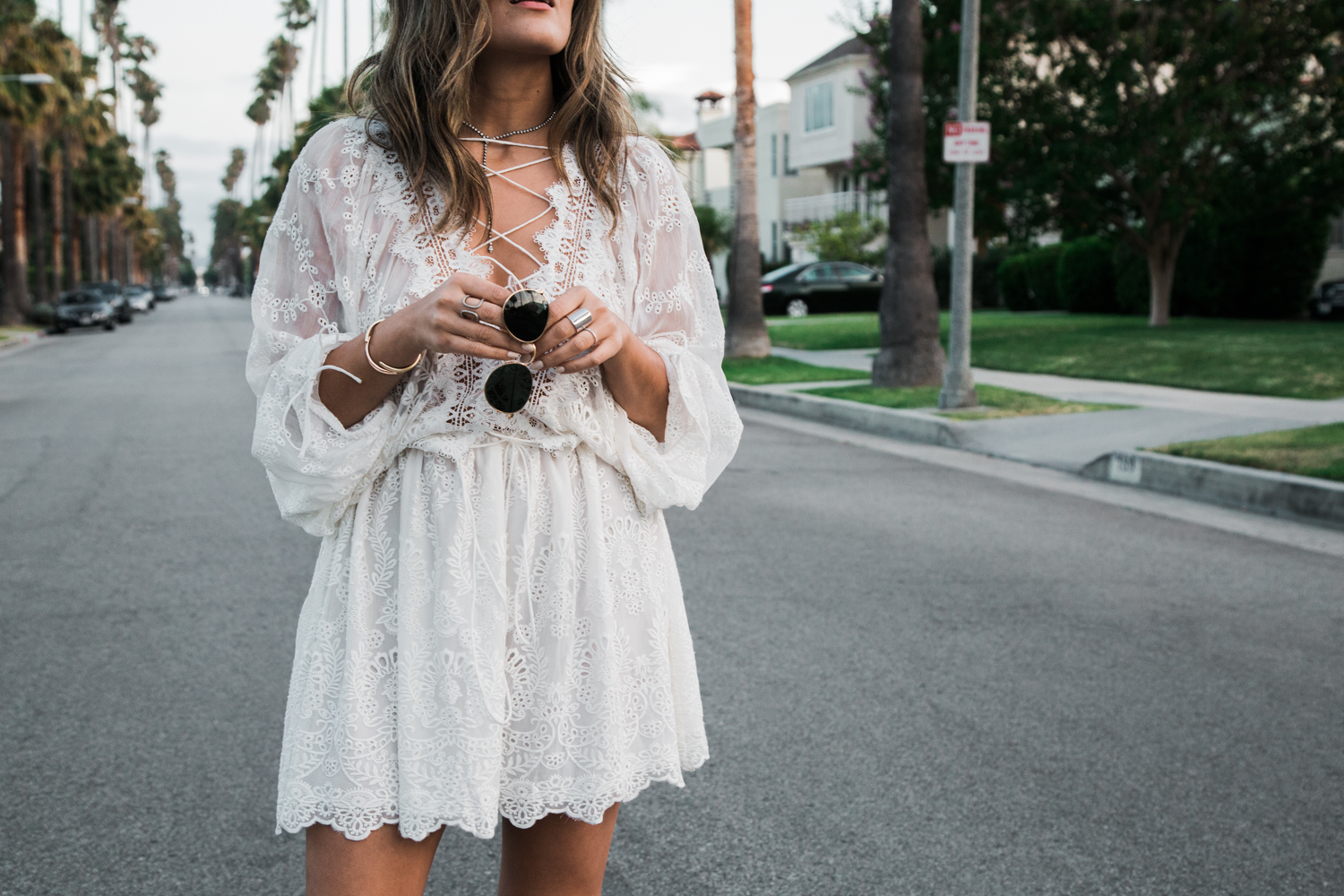 Sara Azani of Style MBA wears a white Zimmermann lace-up dress and ray-ban sunglasses