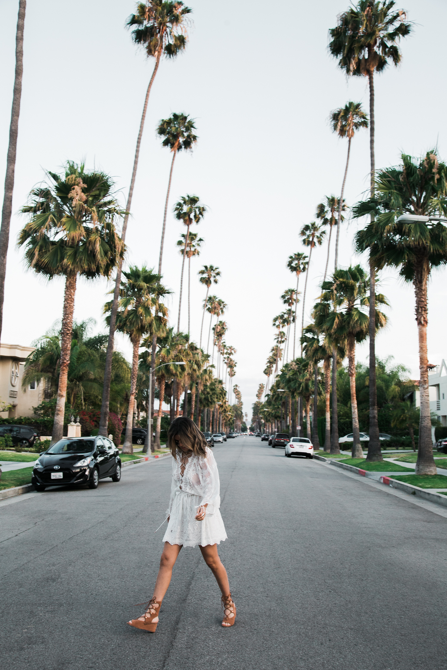 Sara Azani of Style MBA wears a white Zimmermann lace dress with lace up back