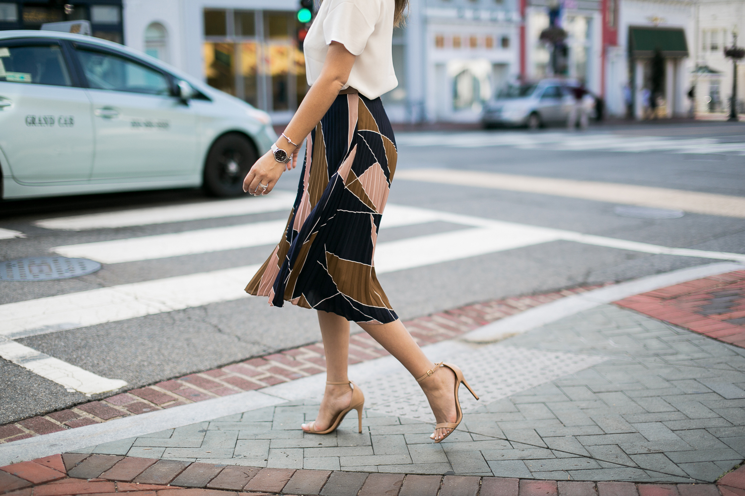 Style MBA wears pleated skirt and nude heels