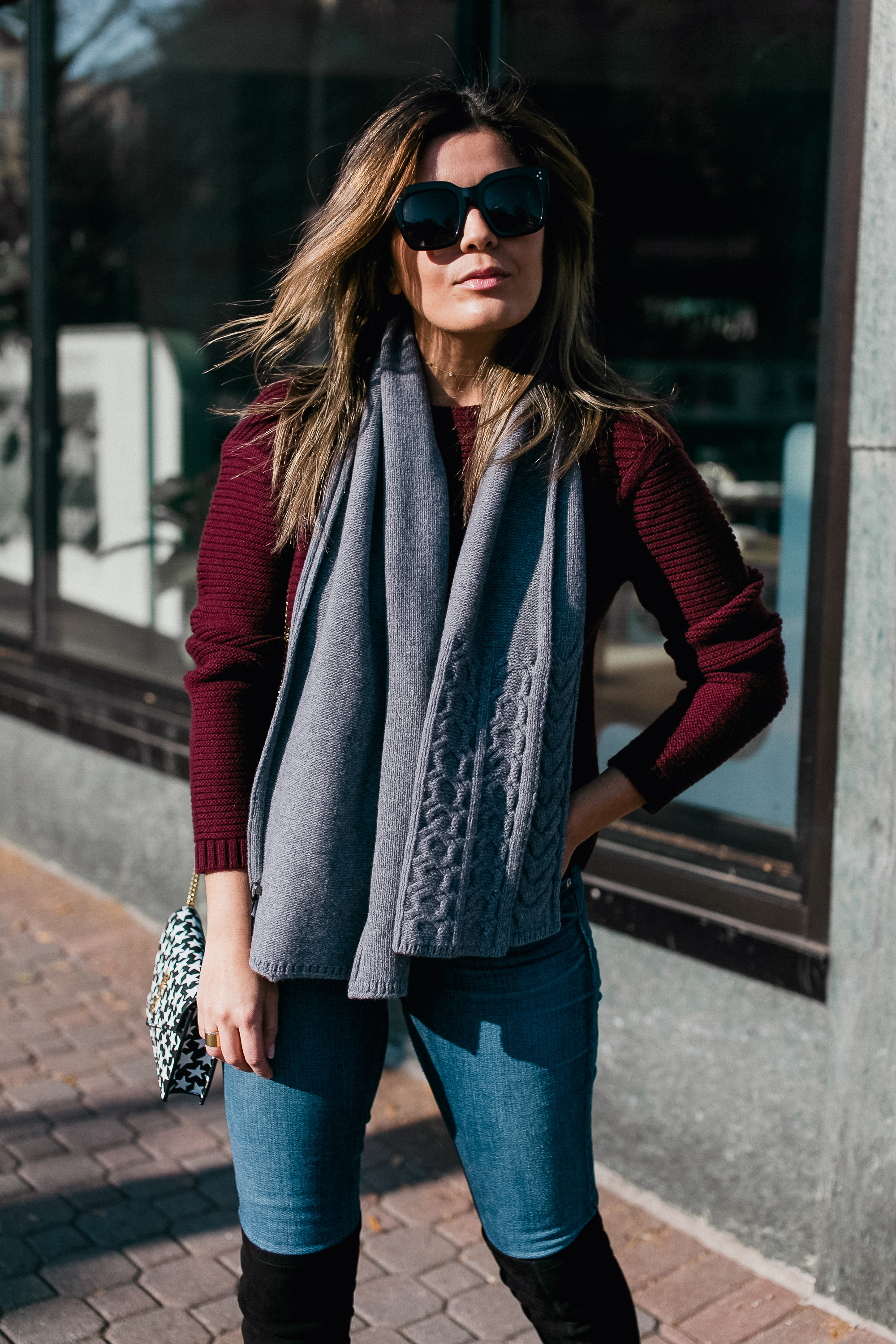 Blogger Sara Azani of Style MBA, a petite brunette woman with blonde highlights, poses outside and wears a Lafayette 148 NY cashmere sweater, Lafayette 148 NY merino cable scarf, and Lafayette 148 NY OTK or over-the-knee boots, along with Céline sunglasses, and a black Gucci belt as part of her burgundy and grey outfit.