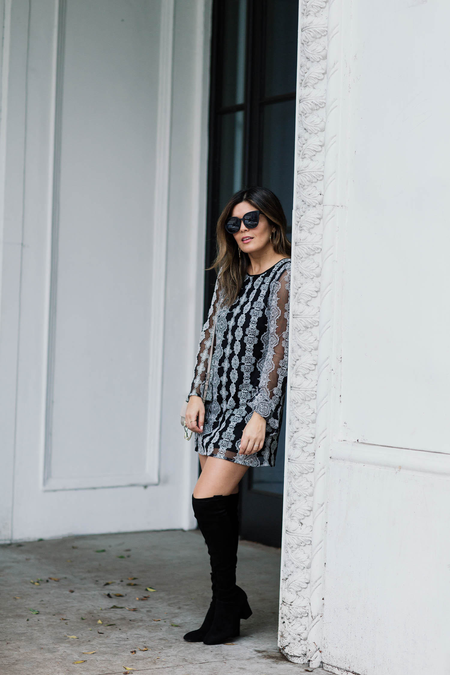 Blogger Sara Azani of Style MBA, a petite brunette woman, wears Band of Gypsies Geometric Print Dress via Nordstrom, Dolce Vita OTK Sparrow Thigh High Almond Toe Boot, Quay Australia Sunglasses, and a Chloé Mini Faye Suede & Leather Wallet on a Chain as part of a black and white outfit.