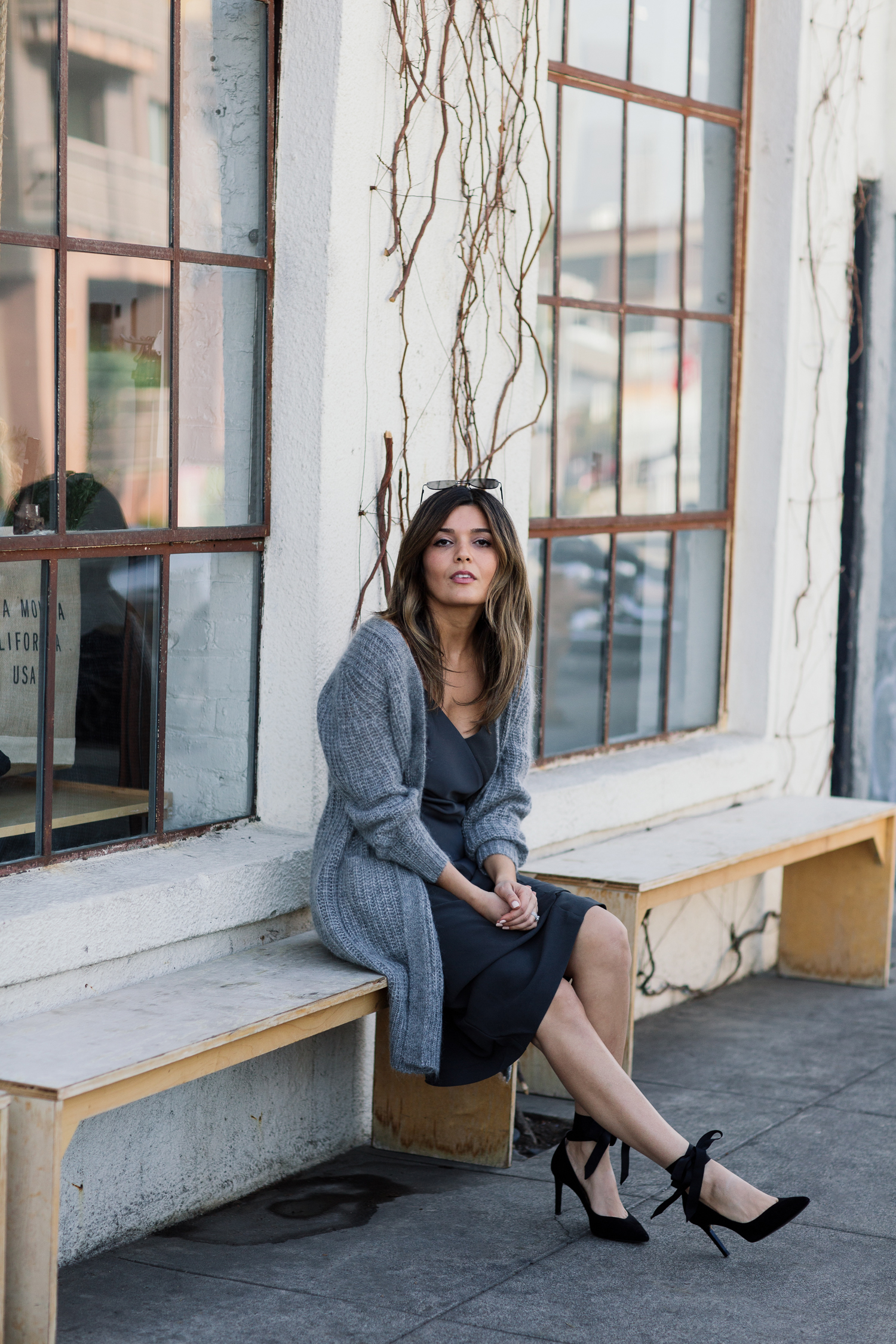 "Detail shot of blogger Sara Azani of Style MBA on a wooden bench outside of a modern warehouse building wearing a Banana Republic Long Open Front Cardigan and black knit foil ""satin"" slip dress, and Maisy Ribbon Tie Pumps in a black and grey outfit accessorized with a Banana Republic clutch purse and minimal jewelry, in front of a modern industrial building."