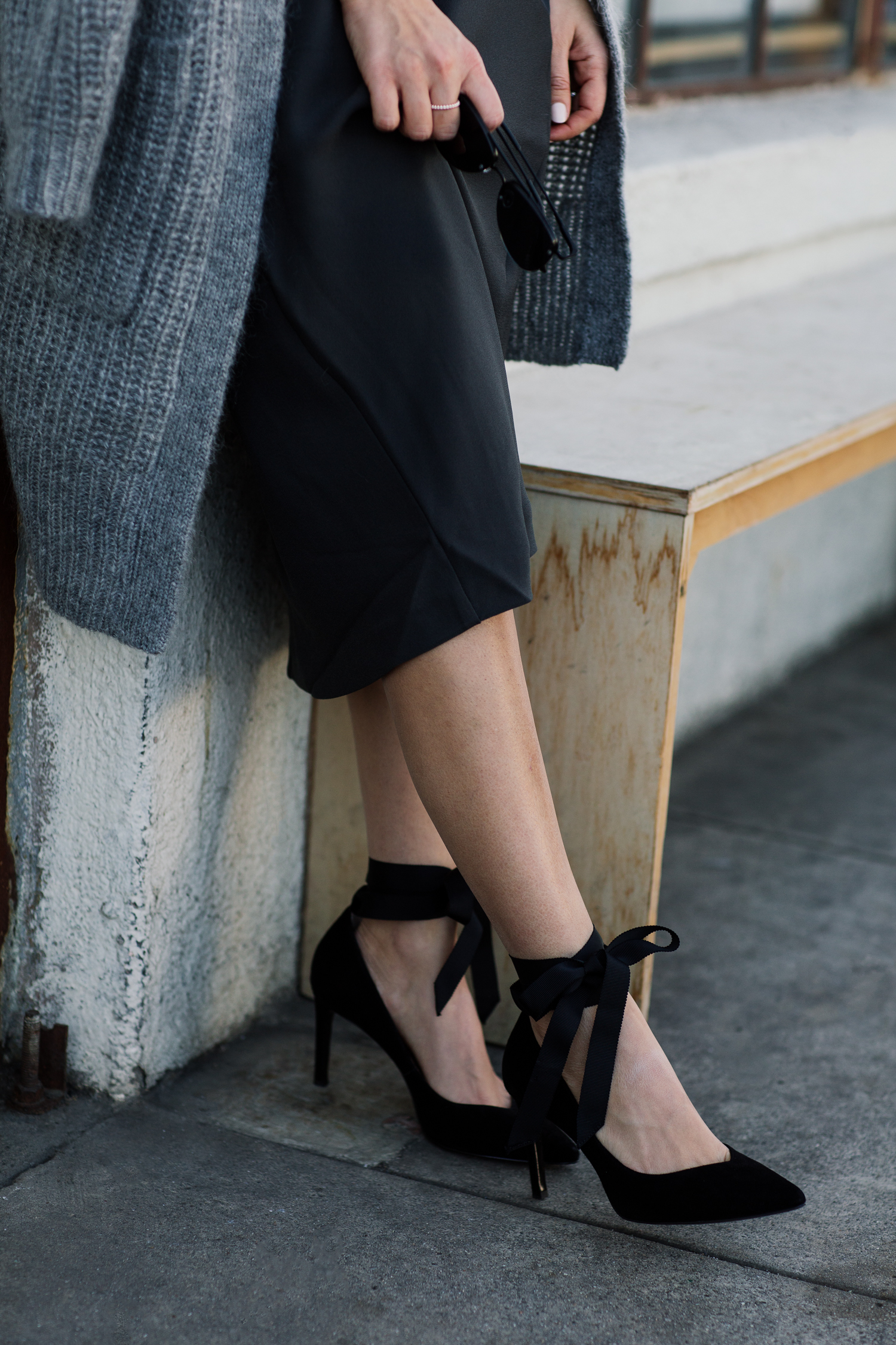 """Detail shot of blogger Sara Azani of Style MBA wears a Banana Republic Long Open Front Cardigan and black knit foil """"satin"""" slip dress, and Maisy Ribbon Tie Pumps in a black and grey outfit accessorized with a Banana Republic clutch purse and minimal jewelry in front of a modern industrial building."""