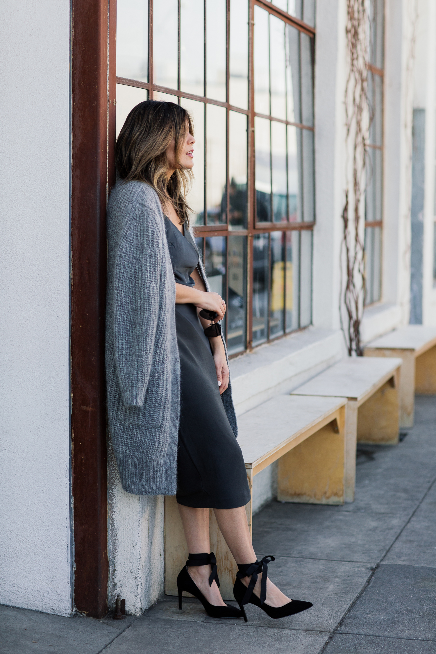 "Detail shot of blogger Sara Azani of Style MBA wears a Banana Republic Long Open Front Cardigan and black knit foil ""satin"" slip dress, and Maisy Ribbon Tie Pumps in a black and grey outfit accessorized with a Banana Republic clutch purse and minimal jewelry in front of a modern industrial building."