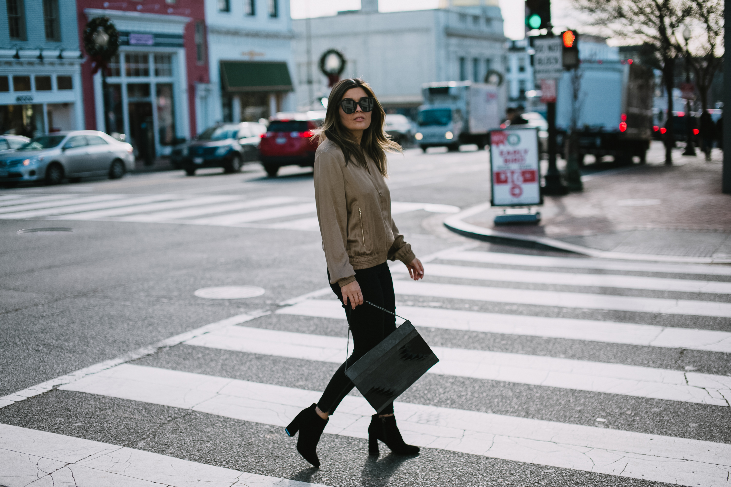 Blogger Sara Azani of Style MBA is photographed wearing Lafayette 148 New York Bryant satin bomber jacket, Quay Australia black oversize sunglasses, J Brand Coated Skinny Jeans, Target paisley booties, and limited edition ITA for Lafayette 148 New York Shantou Pouchette purse. Petite brunette woman wearing simple neutral outfit walking in Georgetown, Washington DC.