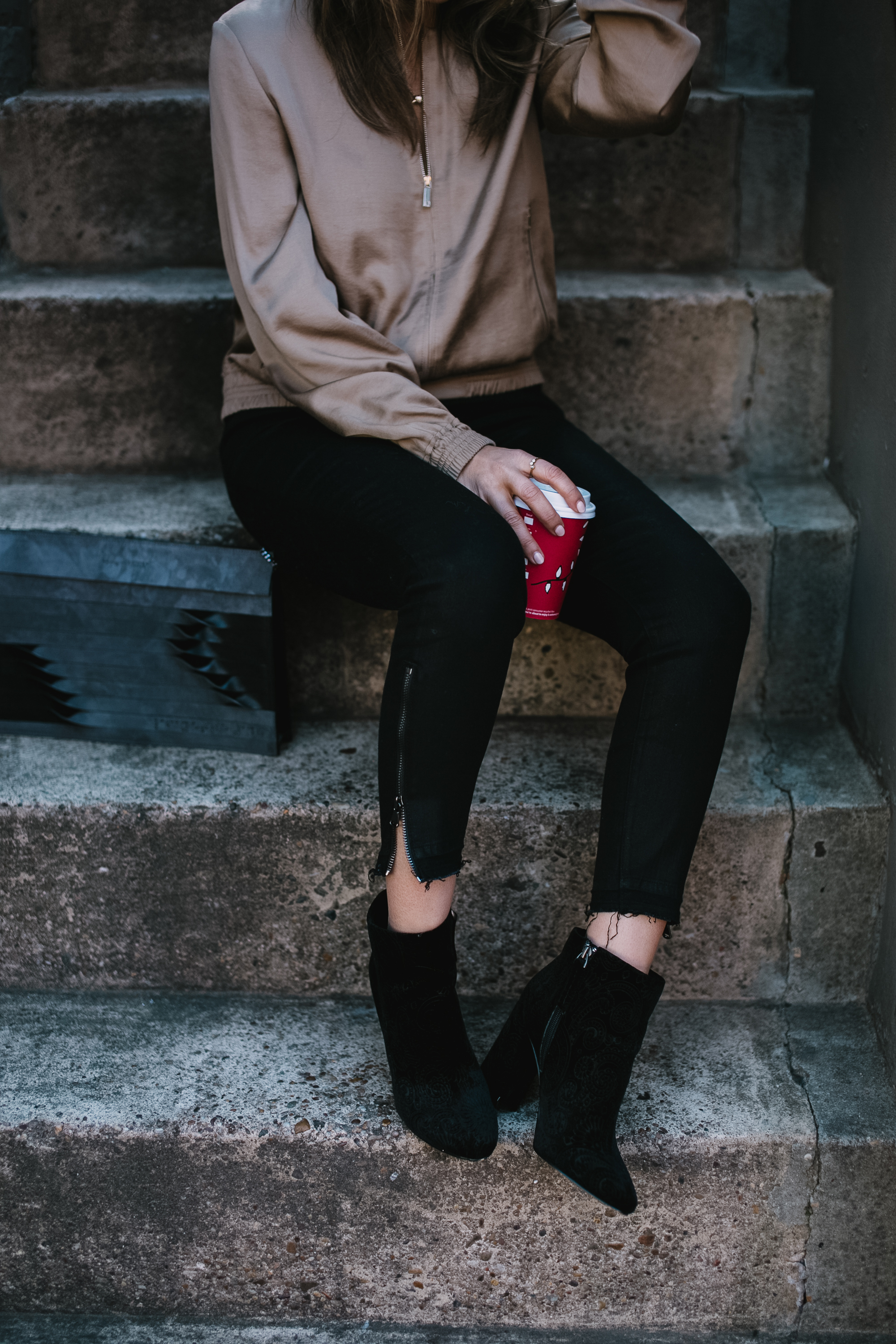 Blogger Sara Azani of Style MBA is photographed wearing Lafayette 148 New York Bryant satin bomber jacket, Quay Australia black oversize sunglasses, J Brand Coated Skinny Jeans, Target paisley booties, and limited edition ITA for Lafayette 148 New York Shantou Pouchette purse. Petite brunette woman wearing simple neutral outfit holding a small coffee while sitting in an outdoor stairwell.