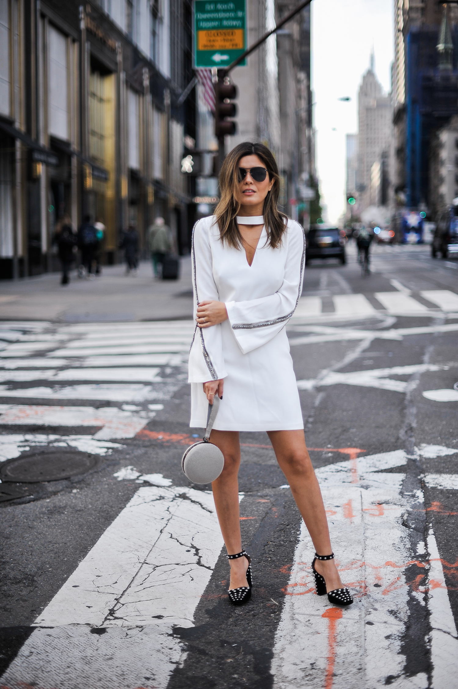 "Blogger Sara Azani of Style MBA wears a white Ramy Brook Lylia Dress (one of her Top 5 NYE dress picks), black studded Alexander Wang ""Elise"" Pumps, black sunglasses, and a Whiting and Davis Canteen Wristlet, at a crosswalk on the streets of New York City."