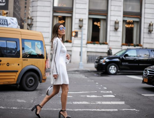 "Blogger Sara Azani of Style MBA wears a white Ramy Brook Lylia Dress (one of her Top 5 NYE dress picks), black studded Alexander Wang ""Elise"" Pumps, black sunglasses, and a Whiting and Davis Canteen Wristlet, at a crosswalk on the busy streets of New York City."