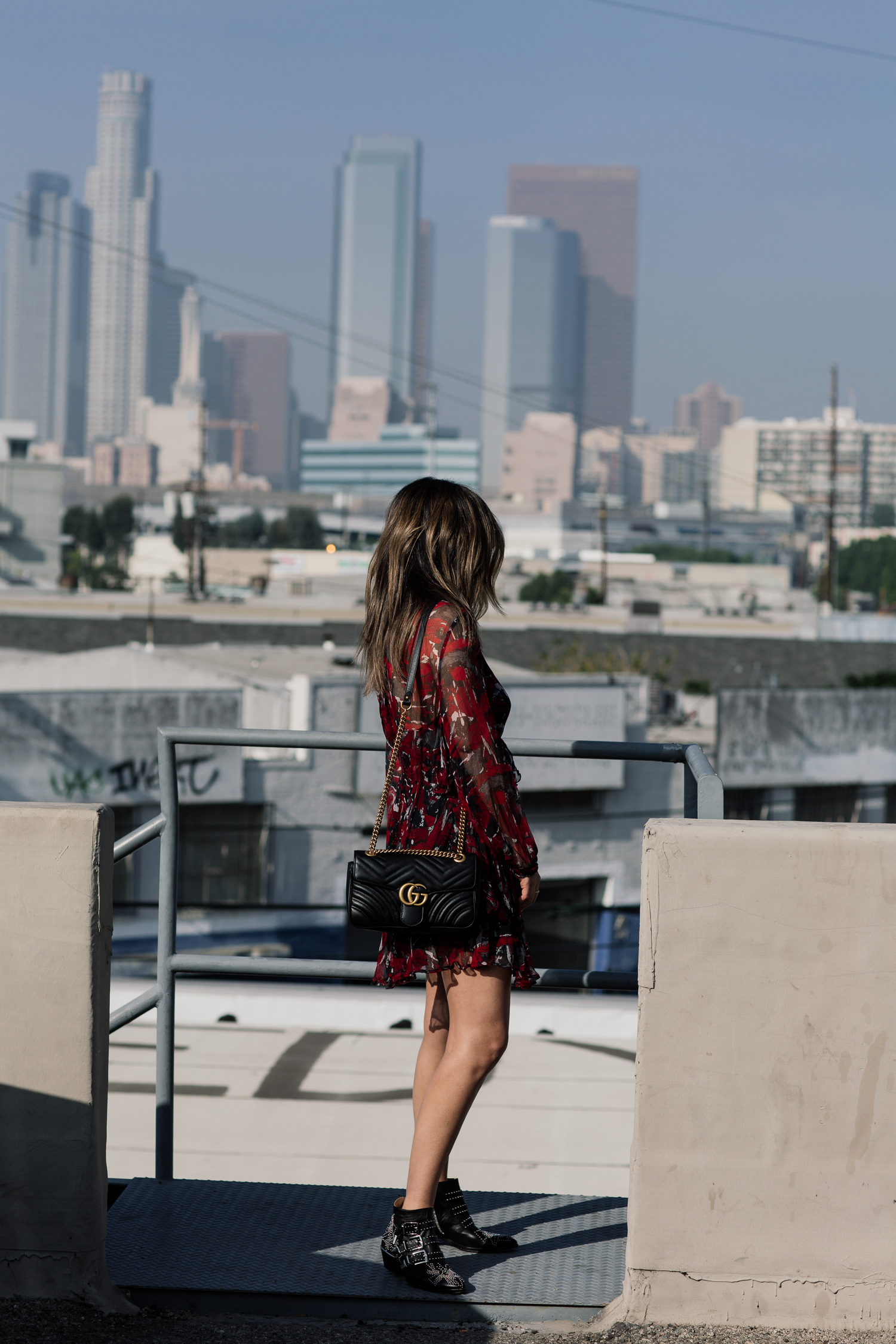 Back detail of red dress worn by brunette woman, blogger Sara Azani of Style MBA is photographed outside in front of a cityscape during the daytime wearing an IRO little red dress, Gucci GG Marmont quilted leather shoulder bag with gold hardware, Chloé Susanna Stud Buckle Booties.