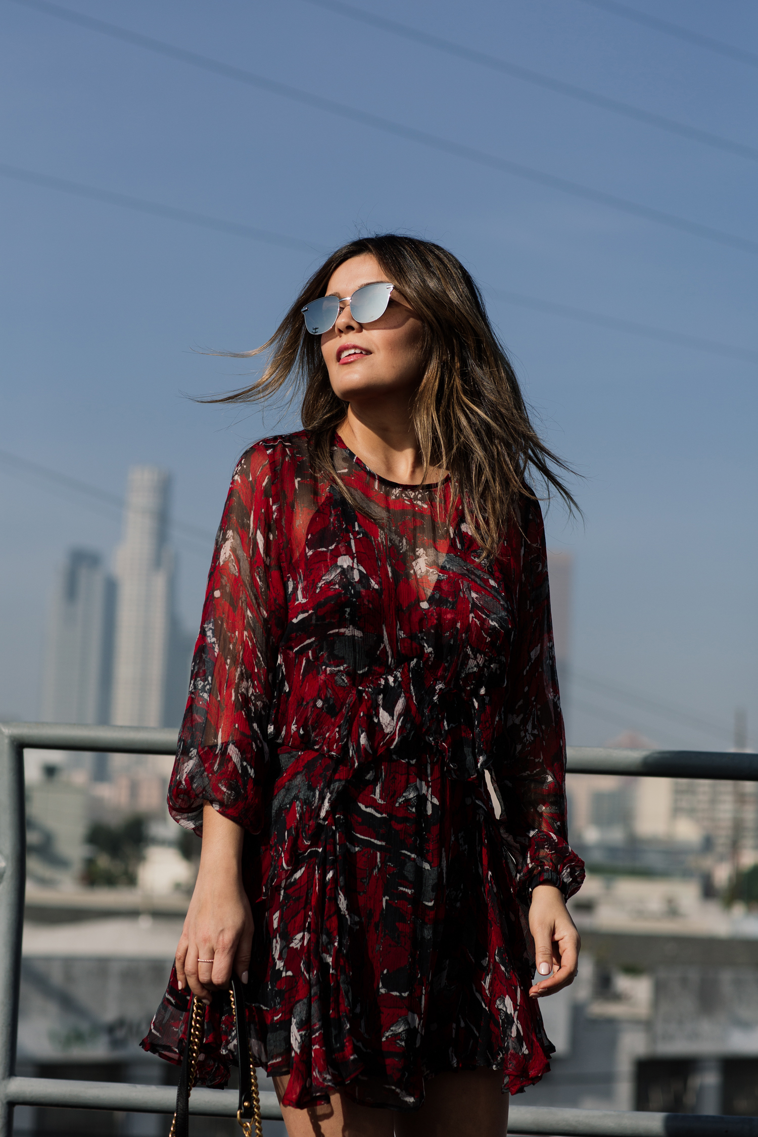 Brunette woman, blogger Sara Azani of Style MBA poses outside in front of a cityscape during the daytime wearing an IRO little red dress, Gucci GG Marmont quilted leather shoulder bag with gold hardware, Chloé Susanna Stud Buckle Booties.