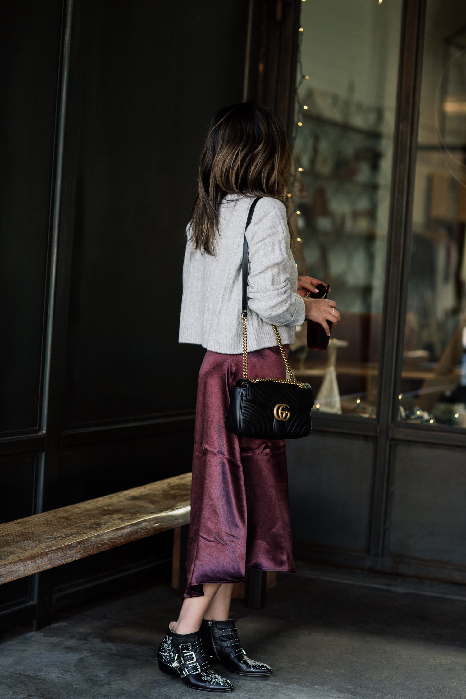Blogger Sara Azani of Style MBA, a petite Brunette woman with blonde highlights wears a satin plum skirt and ribbed sweater from H&M, Chloé Susan Studded Buckle Boots, Ray-Ban Caravan Aviator Sunglasses, and a black leather Gucci shoulder bag outside of a charming café.