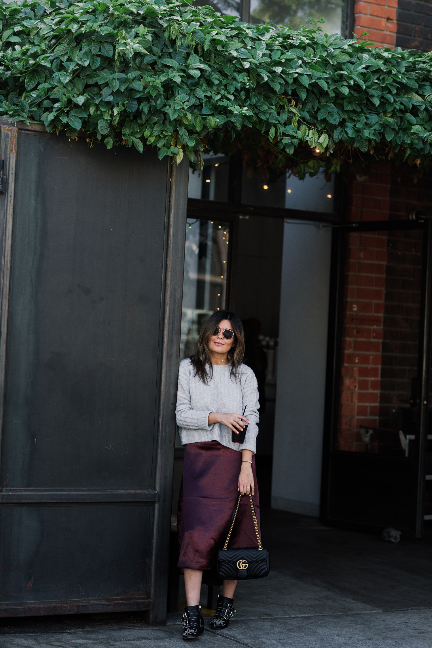 Blogger Sara Azani of Style MBA, a stylish petite brunette woman with blonde highlights holding iced coffee wears a satin plum skirt and ribbed sweater from H&M, Chloé Susan Studded Buckle Boots, Ray-Ban Caravan Aviator Sunglasses, and a black leather Gucci shoulder bag outside of a charming café.