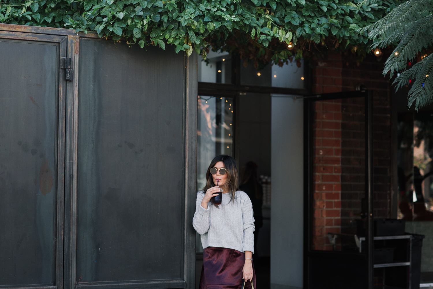 Blogger Sara Azani of Style MBA, a stylish petite brunette woman with blonde highlights drinking iced coffee wears a satin plum skirt and ribbed sweater from H&M, Chloé Susan Studded Buckle Boots, Ray-Ban Caravan Aviator Sunglasses, and a black leather Gucci shoulder bag outside of a charming café.