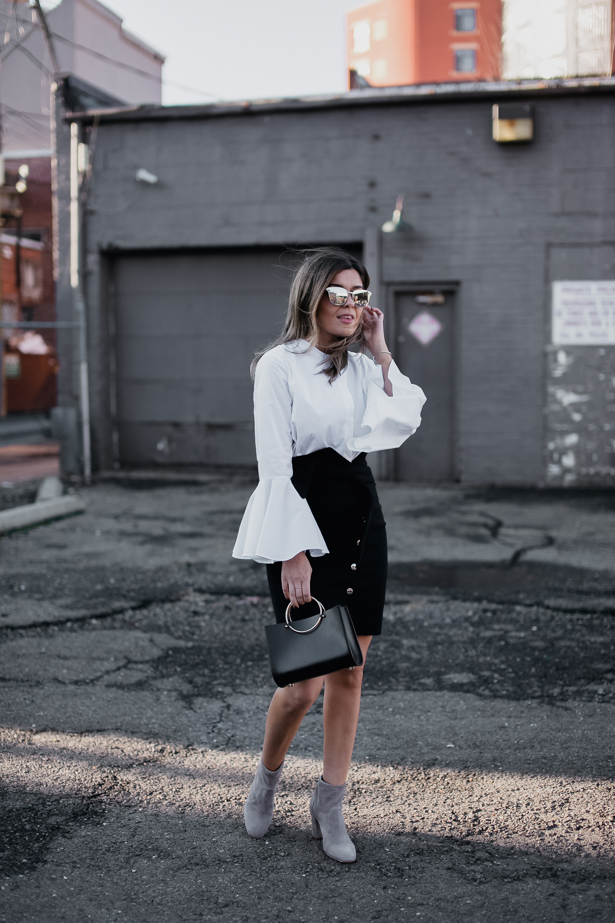 Blogger Sara Azani of Style MBA, a petite Brunette woman with blonde highlights wears the Maddy Assymetrical Button Front Pencil High Waisted Skirt by IRO in black, paired with a white Sotrets dress that is worn as a top, and accesorised with a black Future Glory bag, gold Le Specs sunglasses, and grey suede Schutz boots.