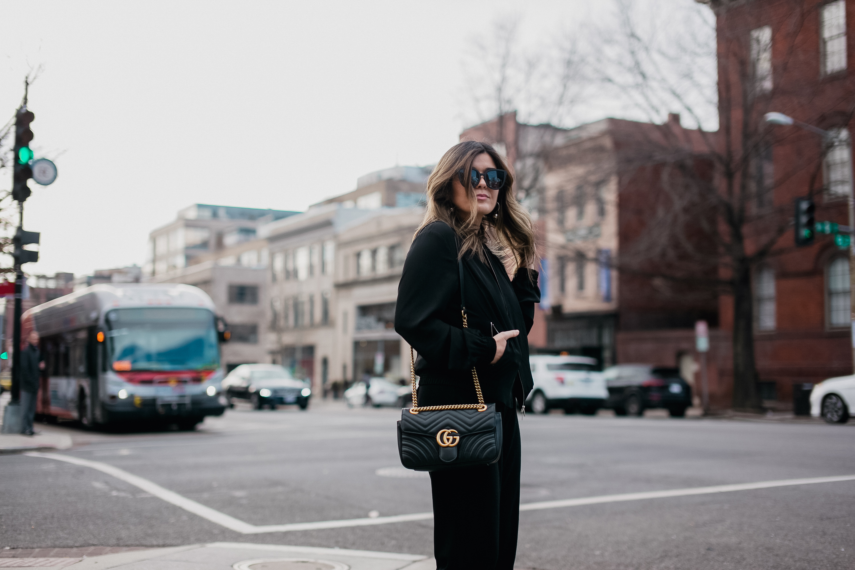 Blogger Sara Azani of Style MBA, a petite Brunette woman, is photographed on the street wearing an all-black outfit featuring Quay Australia black sunglasses, Stuart Weitzman black strappy heels, a black Gucci bag, black cashmere flannel draw-string pants, and a silky black bomber jacket by Lafayette 148.