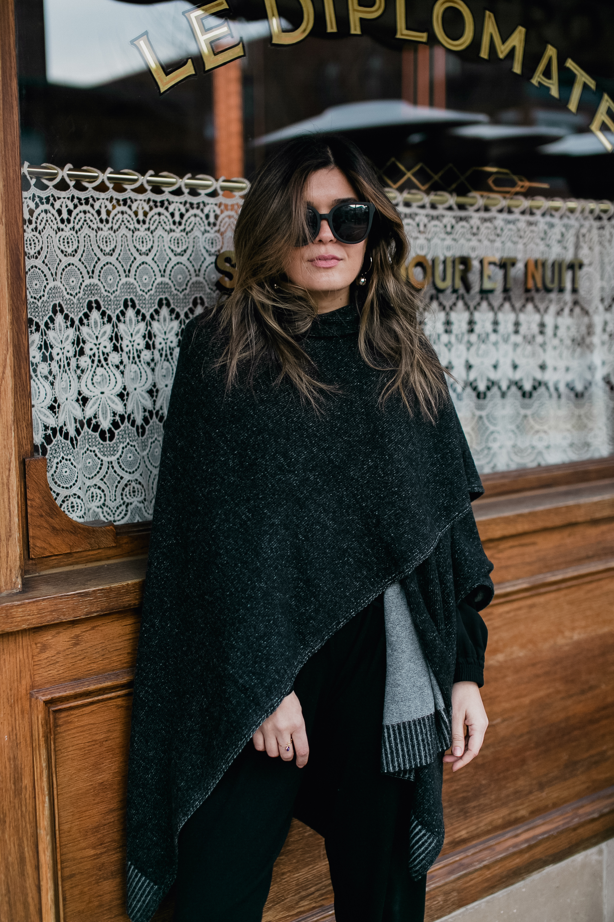 Blogger Sara Azani of Style MBA, a petite Brunette woman with blonde highlights is photographed in front of Le Diplomate restaurant in Washington DC wearing an all-black outfit featuring Quay Australia black sunglasses, Stuart Weitzman black strappy heels, a black Gucci bag, black cashmere flannel draw-string pants, and a silky black bomber jacket layered with a cozy cashmere cape all by Lafayette 148.