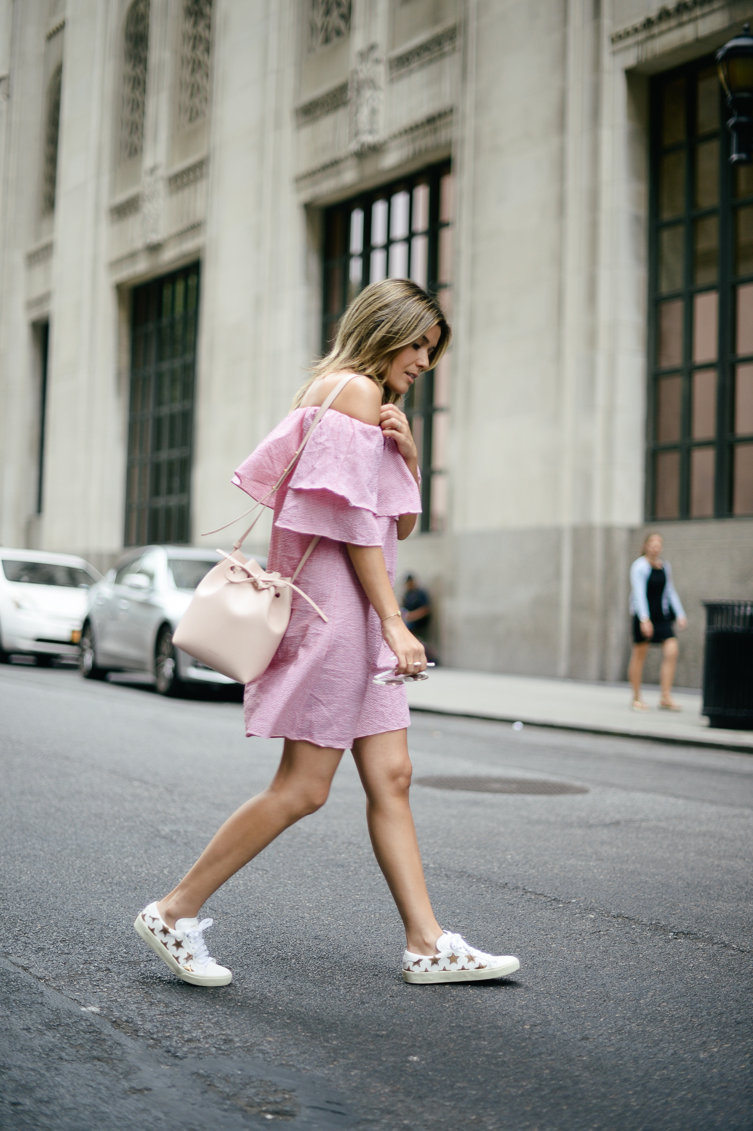 Sara Azani of Style MBA wears a pink ruffle sleeve dress and Saint Laurent leather sneakers as part of an ensemble for her top 10 picks of the Net-A-Porter sale.